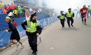 Police and runners react following two explosions at the Boston Marathon finish area.