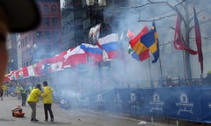 Officials react as the first explosion goes off on Boylston Street near the finish line of the 117th Boston Marathon.