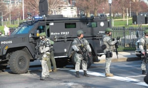 Armed police patrol the area near the site of two explosions at the Boston Marathon.