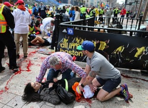 Boston explosions update: An injured woman is tended to at the finish line of the Boston Marathon