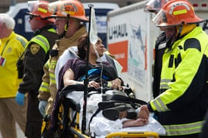 Boston explosions update: Emergency responders help an injured woman on a stretcher