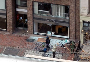 Boston explosions update: A man in a bomb-disposal suit investigates the site of an explosion on Boyl