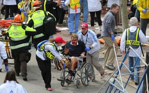 Boston explosions update: A person who was injured is taken away from the scene in a wheelchair