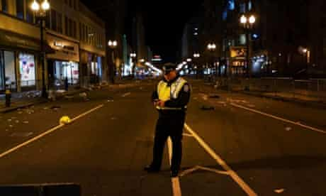 A Boston police officer stands near the scene of the twin bombing at the Boston Marathon late night in the city. Three people are confirmed dead and at least 141 injured.
