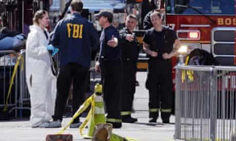 Boston firefighters talk with FBI agents and a crime scene photographer at the scene of Monday's Boston Marathon explosions.