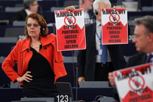 "Members of the Group of the European United Left of the European Parliament hold posters with the slogan ""Hands off Cyprus, Portugal, Greece, Spain, Ireland"" during a debate on the situation in Cyprus at the European Parliament in Strasbourg, April 17, 2013."