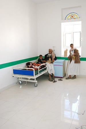 Ali Abdulla waits with his four-year-old son Ahmad, who is recovering from pneumonia