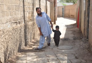 Polio victim Usman Shangla, aged 32, and his son in Pakistan
