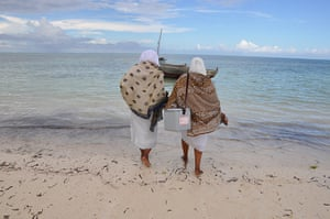 Health workers carrying vaccines wade out to a sailing boat in Zanzibar