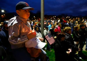 A young boy holds a lit candle and an American flag atop his father's shoulders during a vigil for eight-year-old Martin Richard, from Dorchester, who was killed by an explosion near the finish line of the Boston Marathon on April 16, 2013 at Garvey Park in Boston, Massachusetts.