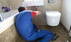 A plumber fixes a bathroom sink