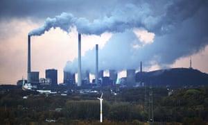 A coal-fired power station in Gelsenkirchen, Germany dwarfs a wind turbine  in the