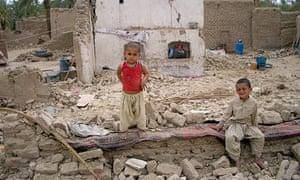 Two children sit near their destroyed mud brick house in Mashkel, the hardest hit area