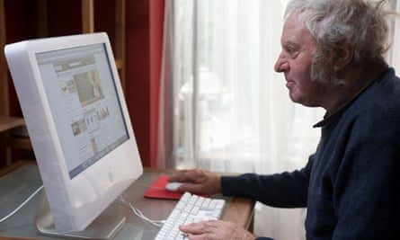 Elderly man at home using a computer to access the internet, Suffolk, UK.