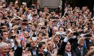 Spectators take pictures with their smartphones as they watch a parade celebrating Britain's athlete