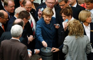 German Chancellor Angela Merkel, center, casts her vote during meeting of the German federal parliament, Bundestag, in Berlin, Germany, Thursday, April 18, 2013.