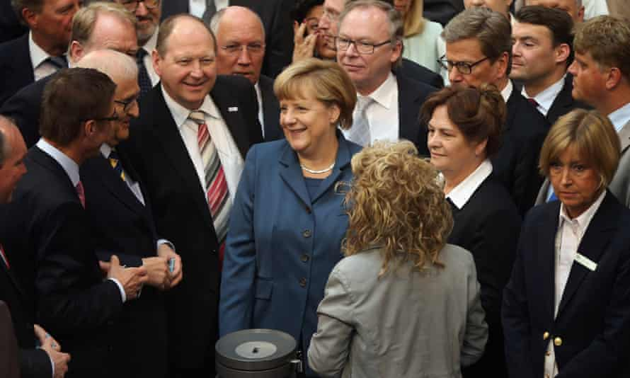 German Chancellor Angela Merkel chats with colleagues prior to voting on EU finanical aid to Cyprus at the Bundestag on April 18, 2013 in Berlin, Germany.
