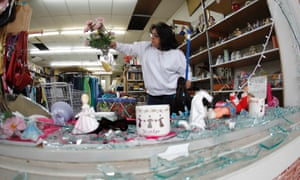 Maria Galvan looks at damaged merchandise as she cleans up at a store near to explosion site of fertilizer plant on April 18, 2013 in West, Texas.