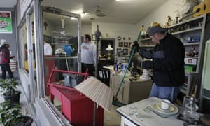Workers clean up shattered windows at a store near to explosion site of fertilizer plant on April 18, 2013 in West, Texas.