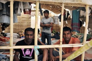Migrant workers sit inside a makeshift camp in Nea Manolada on April 18, 2013.