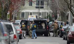 FBI agents prepare to enter an apartment building reported to be the residence of the two men who bombed the Boston Marathon