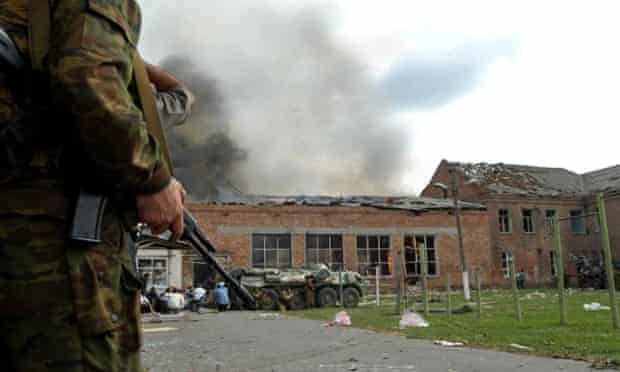 Soldiers and security forces are seen in front of a burning school in Beslan, nortern Ossetia, 03 September 2004