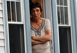 A woman looks out from her door as police search the area in Watertown, Massachusetts April 19, 2013.