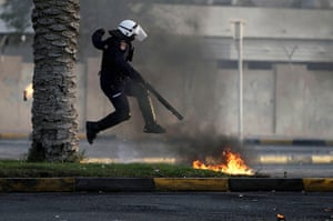 24 hours in pictures: Diraz, Bahrain: A riot policeman avoids petrol bombs thrown by Bahraini ant