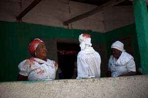 24 hours in pictures: Souvenance, Haiti: Voodoo believers wearing white clothing stained with blo