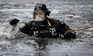 A diver breaks ice while he searches for a man thought to have fallen through the ice into Dow Loch in Scotland. Emergency services were called to the remote Dow Loch in the Cleish area of Perthshire at 3pm yesterday.