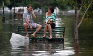 Residents sit on a bench in a flooded public square after a rainstorm in Buenos Aires. Thunderstorms damaged property and vehicles, cut power and caused delays on flights in Buenos Aires and its suburbs today.