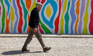 A man walks past a painted wall in Ericeira village north of Lisbon in a sunny Portugal today. There were floods in the country yesterday.