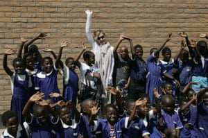 A humanitarian tourist in Africa: US Pop Star Madonna flanked by her adopted Malawian children, David (to her left), Mercy (to her right) and other school children wave outside a classroom at Mkoko Primary School in central Malawi. Photograph: Amos Gumulira/AFP/Getty Images