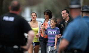 Police officers escort a family away on Franklin Street