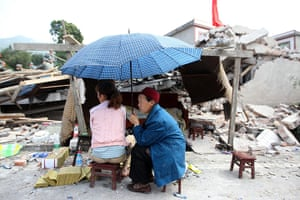 China: A girl gives offerings to the dead by the side of a badly damaged building