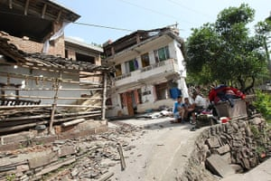 China: Residents rest outside damaged houses in Longmen township