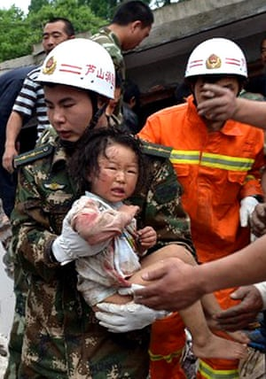China: A rescuer carries a child to safety afte