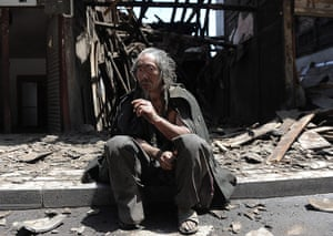 China: A man sits in front of his house, destroyed by the earthquake in China