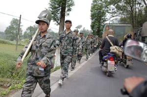 Dan Chung in China: Security personnel equipped with shovels march along the roadside