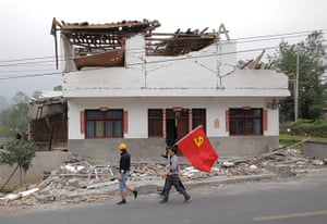 Dan Chung in China: Voluteers wave a Chinese flag as they walk past a building.