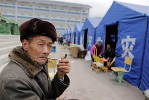 Dan Chung in China: An elderly man smokes a pipe at a temporary campsite in Longmen.