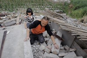 Dan Chung in China: Zhang Yichuan and her father clamber over the ruins of their house to searc