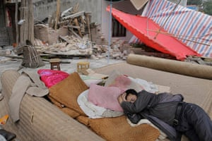 Dan Chung in China: A man attempts to sleep amid the ruined homes.
