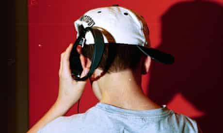 A teenage boy wearing a baseball cap listening to music on headphones