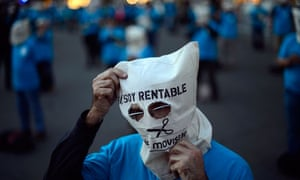 Masked employees from the Telefonica phone company protest in Barcelona, Spain
