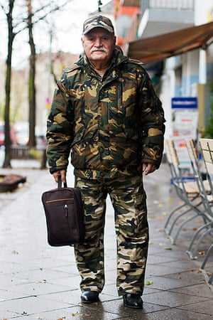 big picture - what ali : man in camouflage suit with hat and holding a bag