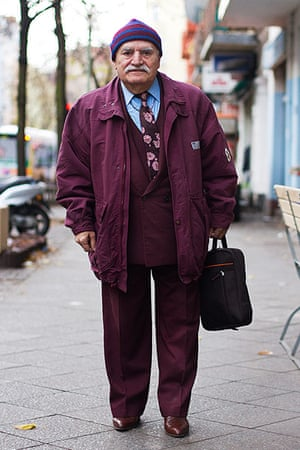 big picture - what ali : man in burgundy jacket, trousers and hat standing in street