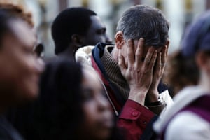 Boston bombings timeline: A mourner reacts during a candlelight vigil at City Hall