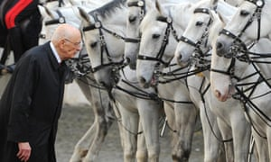 The re-elected Italian President Giorgio Napolitano takes a close interest in the horses of a mounted guard as he is received with military honours at Quirinale Palace in Rome.