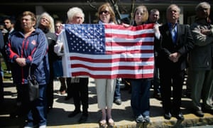 People hold an American flag outside the funeral for Krystle Campbell, who was one of three people killed in the Boston Marathon bombings.